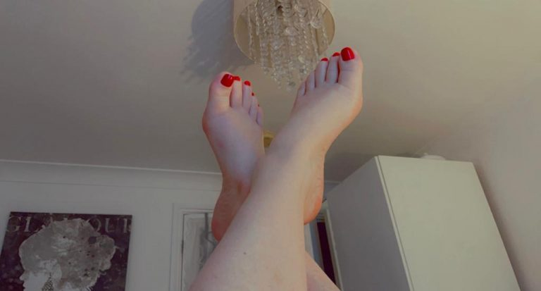 Red toenails on pale perfect feet poised in the air